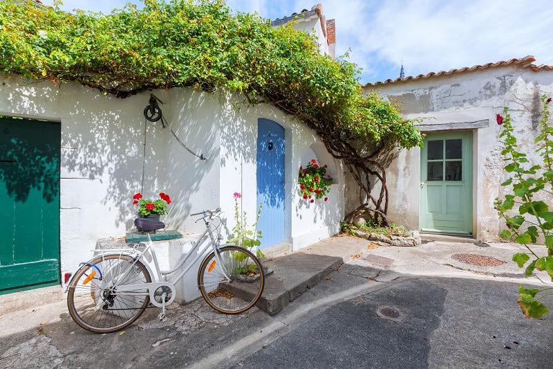 Prenez le temps de découvrir les venelles fleuries de roses trémières au rythme lent des vélos lors de votre séjour en chambre d'hôtes Les Fillattes